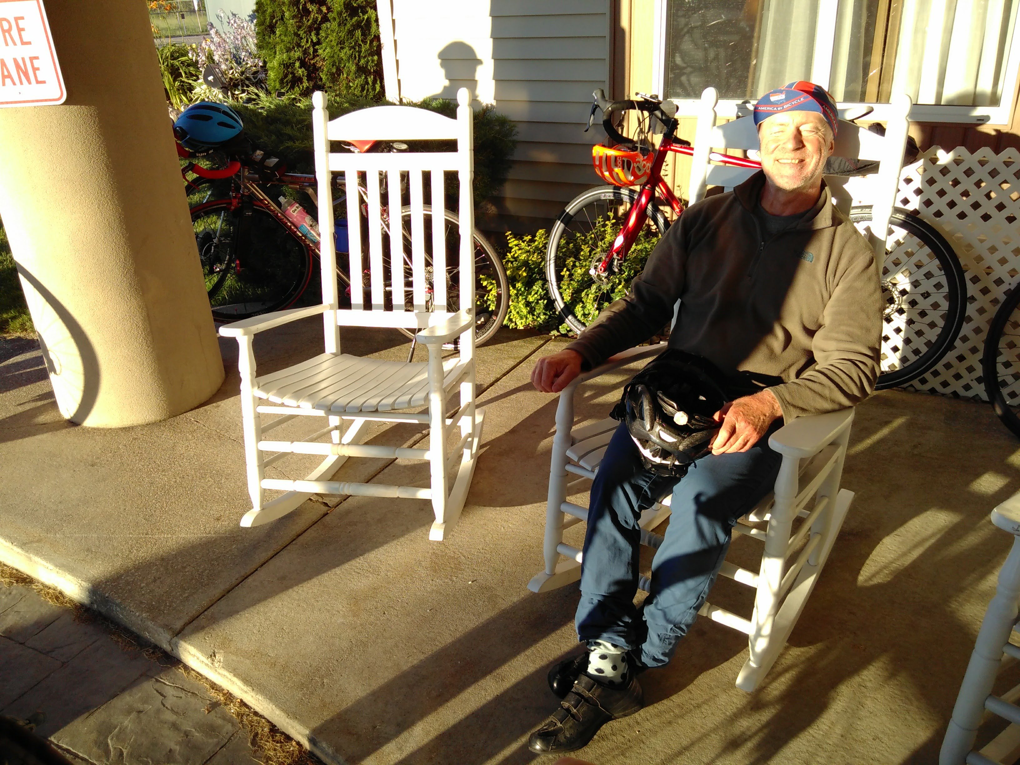 Chris sits in a rocking chair as the sun sets. He has a big grin on his face.