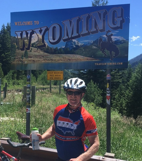 Chris by the Welcome to Wyoming sign