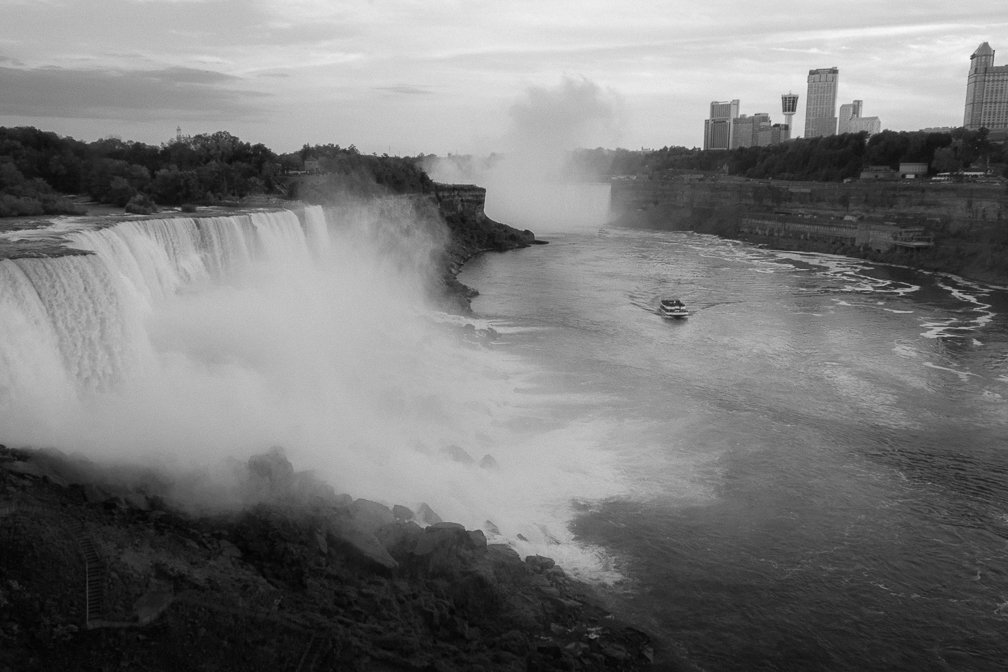 A black and white photo of the falls. The US falls are seen on the left and the horseshoe falls are seen in the distance.