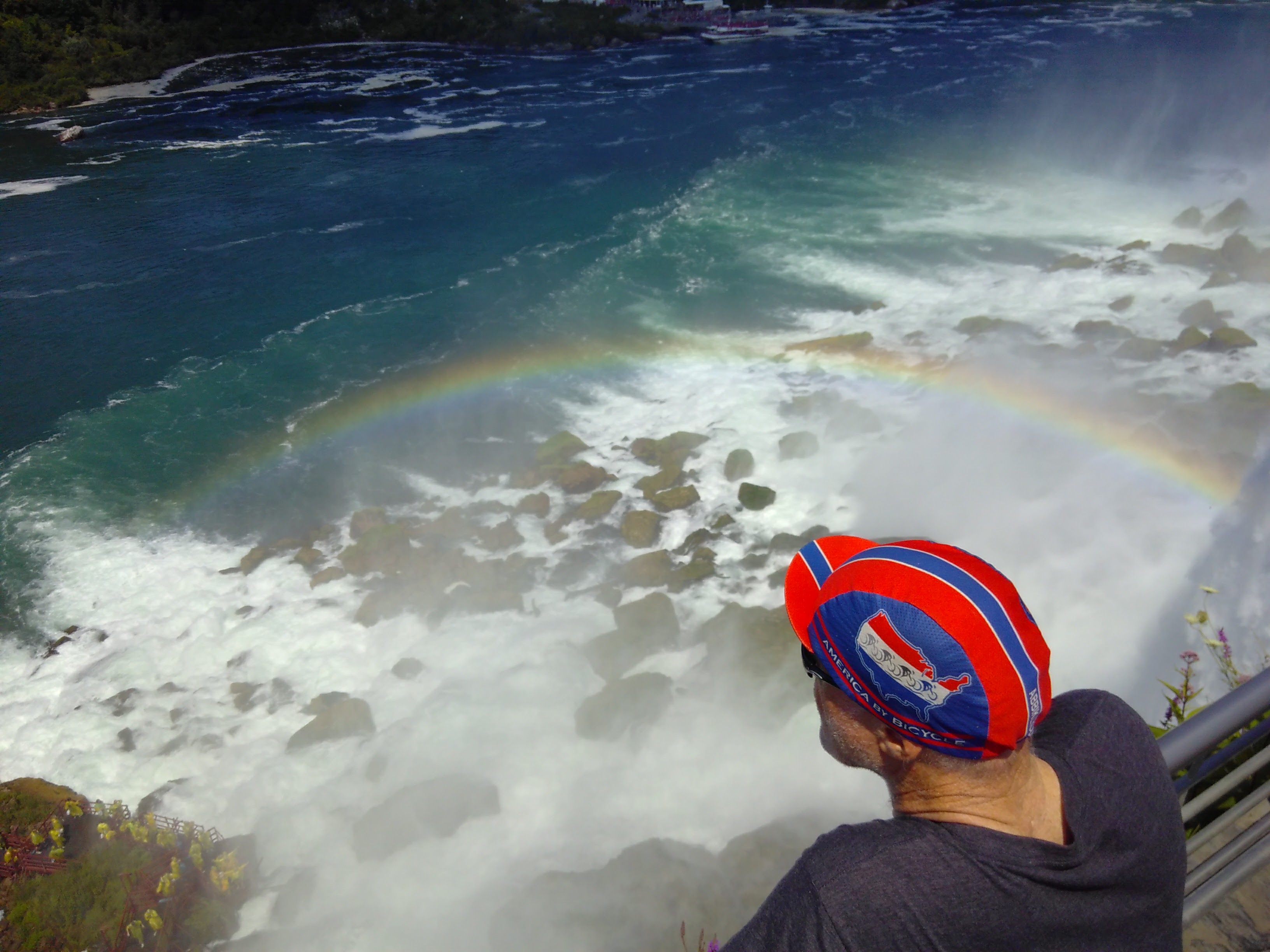 Chris listens to the crashing of the US falls. There is a rainbow around his head.