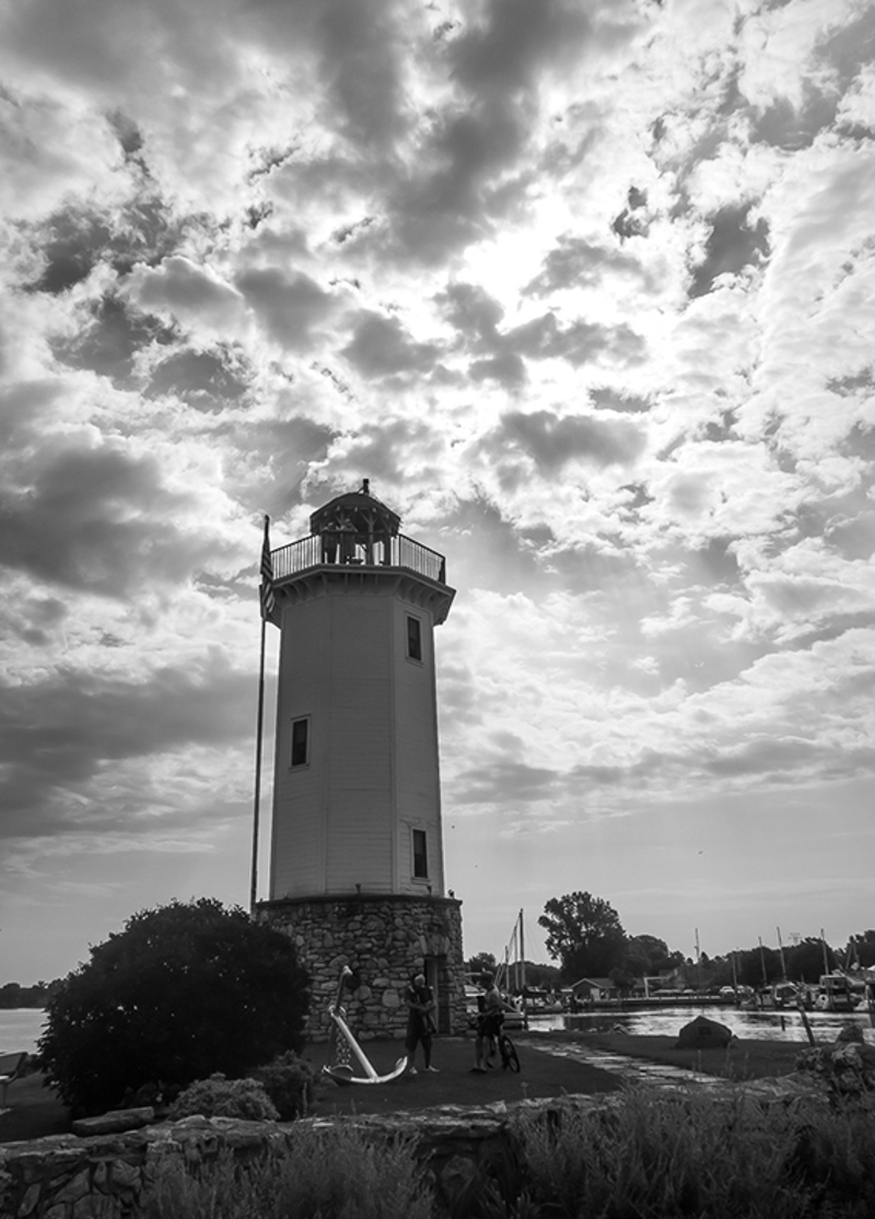 The lighthouse of lake winnebago is shown against a backdrop of clouds with two cyclists looking small in front of it. The photo is in black and white.