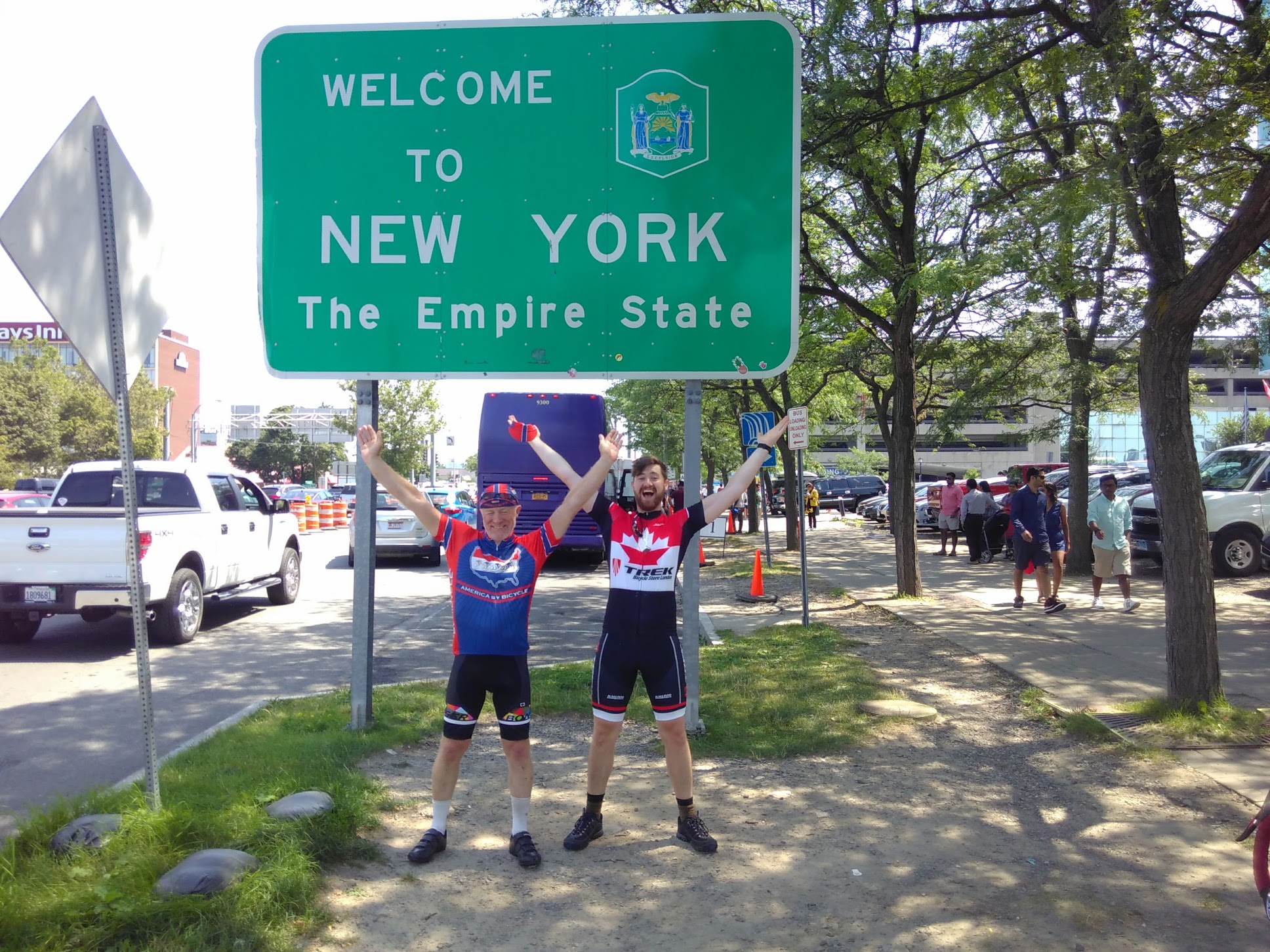 Chris and James make a Y sign with their arms in front of the Welcome to New York sign