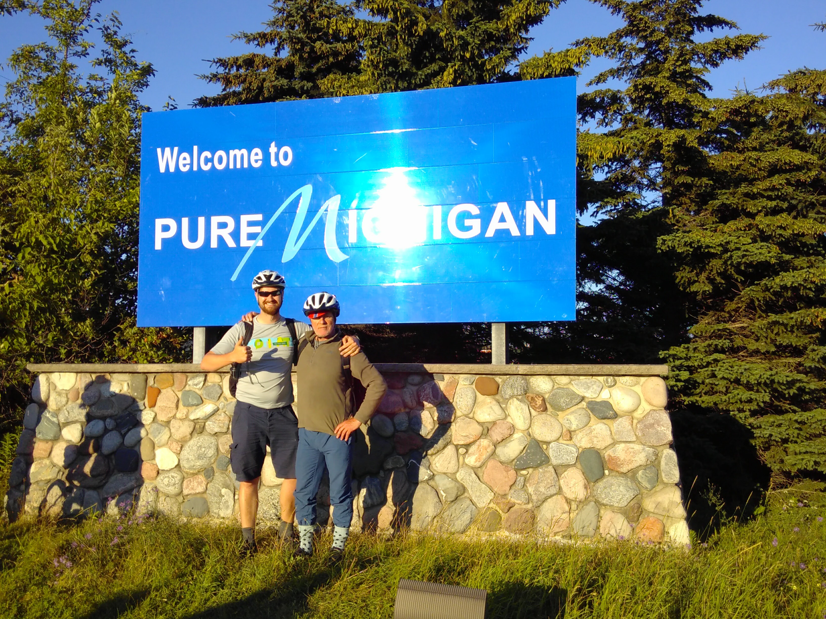 Chris and James are posing in front of a bib blue sign reading: Welcome to Pure Michigan