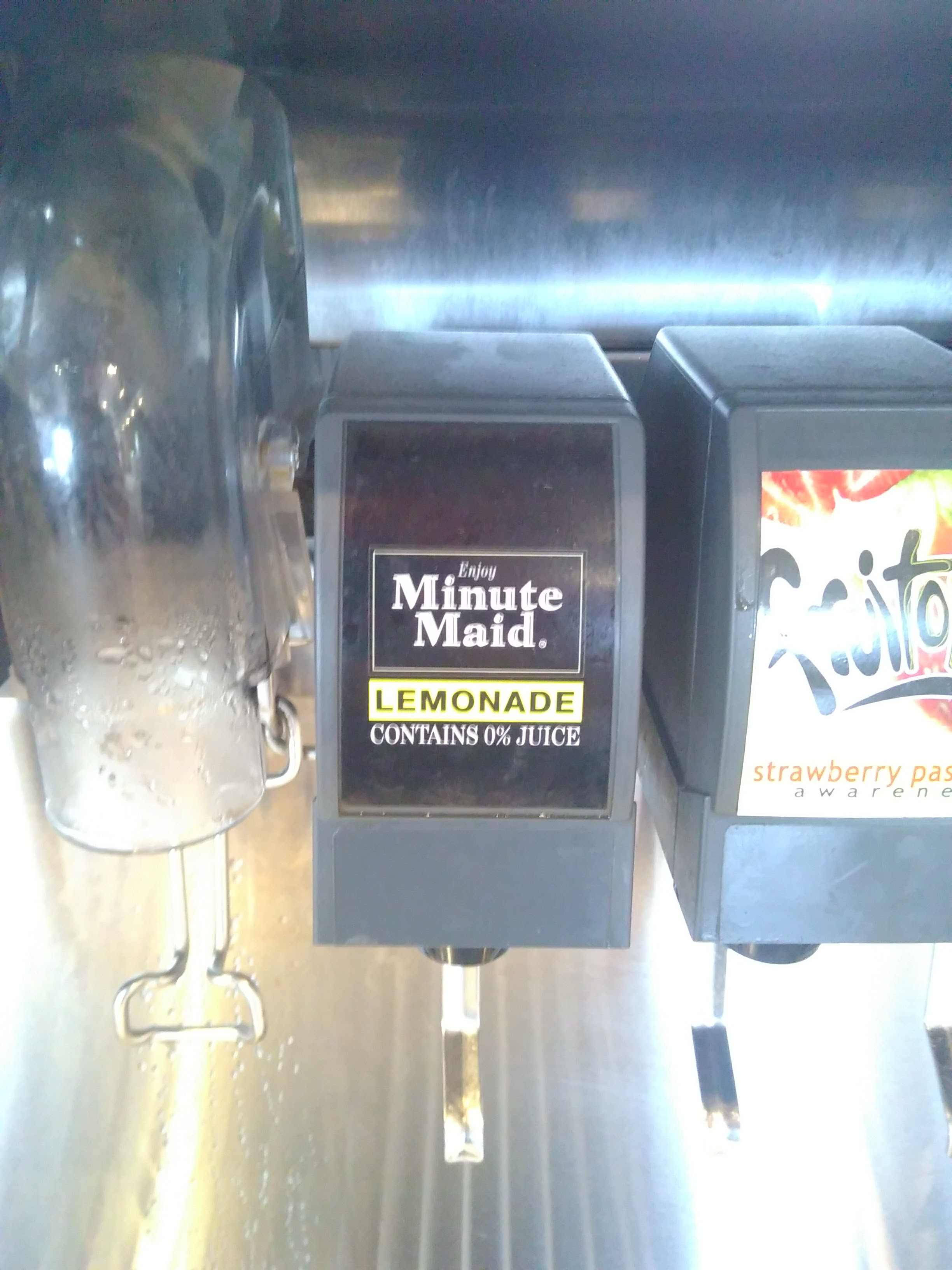 "A drinks dispenser. The label reads: ""Minute Maid Lemonade, 0% Juice"""