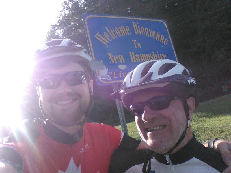 James and Chris pose in front of the Welcome to New Hampshire sign