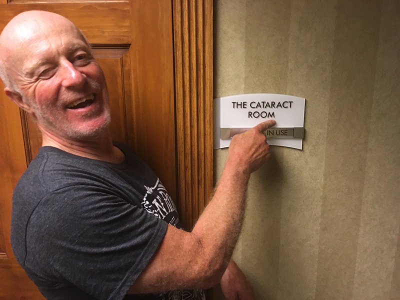 "Chris points to the hotel meeting room sign reading ""Cataract Room"""