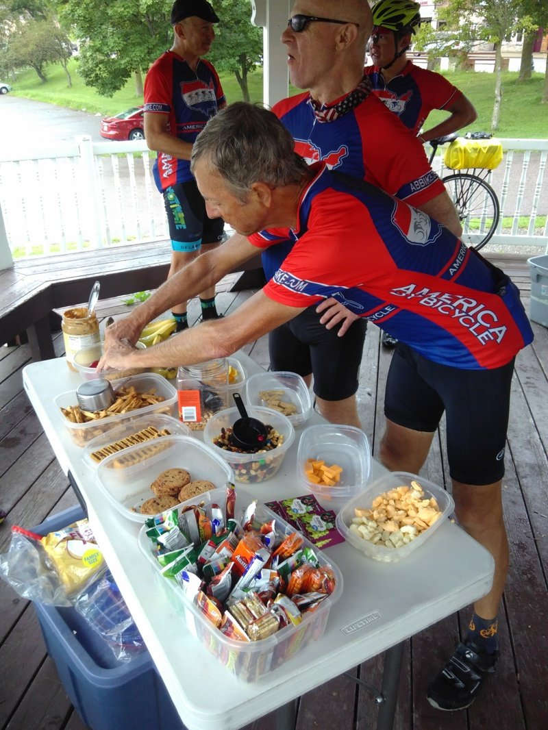 Chris and Judge Ted refuel at a SAG stop. There are cheese curds amongst other sweets and fruit on the table.