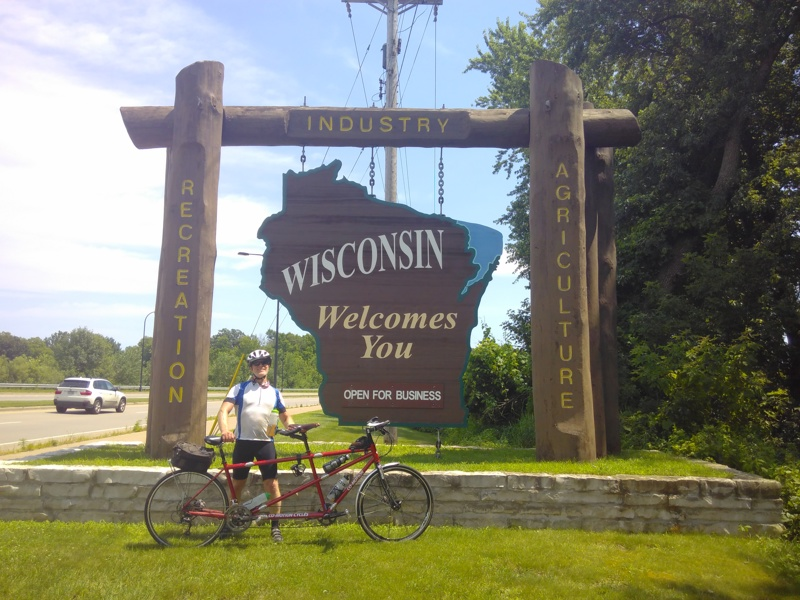 Chris with Genevive in front of the Wisconsin sign