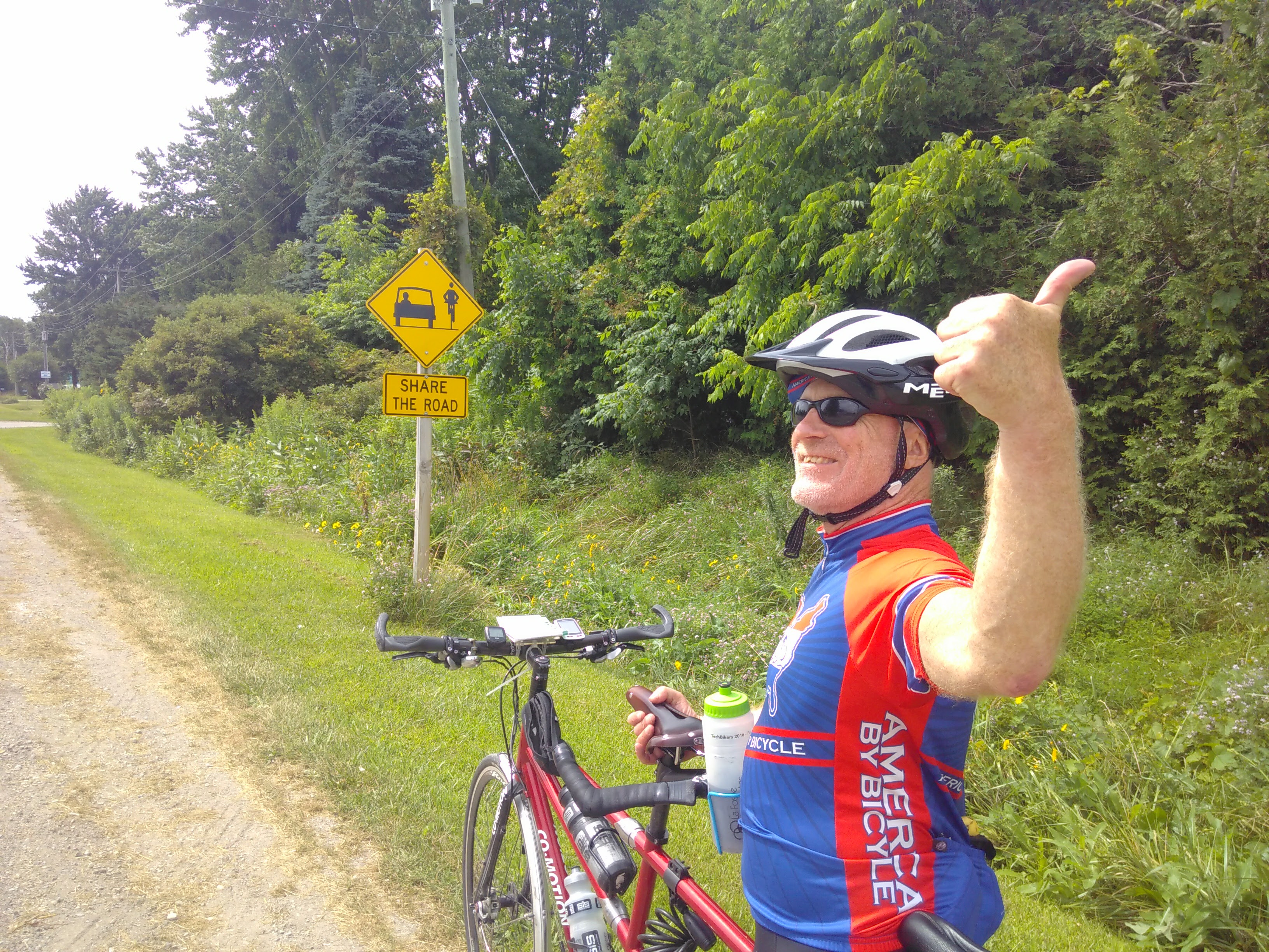 "Chris gives a thumbs up in front of a sign reading ""Share the road"" with a picture of a car and a bicycle"